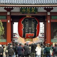 Landmark returns: A crowd gathers Monday to view the newly replaced red lantern at Kaminarimon (Thunder Gate), one of the gateways to popular Sensoji Temple in Tokyo's Asakusa district. | KYODO