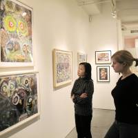 Bird's-eye view: Midori Kano (left), assistant director of Cavin-Morris Gallery in New York, and a visitor view owl-themed paintings by disabled artists from countries including Japan, Nepal, South Korea and Italy on Oct | 23 DURING AN EXHIBITION TITLED