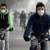 Helmet optional: People bicycle through heavy air pollution in Beijing last month | KYODO