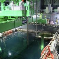Out of their depth?: Workers at the Fukushima No. 1 nuclear plant remove fuel rods from a pool in the reactor 4 building, in a handout picture provided by Tokyo Electric Power Co. on Monday | AFP-JIJI/TEPCO