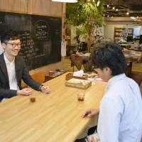 Working together: Fumitaka Suzuki (left), an independent interior designer, talks with a staff member of PoRTaL, a co-working space in Shibuya Ward, Tokyo. | KYODO
