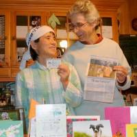 All's well that ends well:  Takako Ueda and her wife, Frances Herbert, show Ueda's U.S. green card along with news stories and letters of support in their  Vermont home last month | KYODO