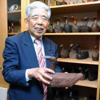 Ducks in a row: Haruo Yahashi holds a bird sculpture, one in his collection that he will donate to a South Korean college. | KYODO