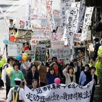Poor man's protest: Demonstrators march in Shibuya Ward, Tokyo, in May to demand enactment of a law to rescue children from poverty.  | KYODO