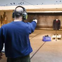 Sharpshooter: A marksman shoots a handgun at a bulletproof jacket made by Garrison Bespoke tailors during a demonstration at a shooting range in Ajax, Ontario, on Nov. 5. The price of the suit, lined with ultrathin sheets of nanotube fiber, starts at 20,000 Canadian dollars | AP