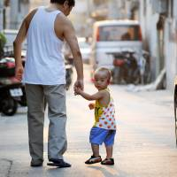 Parental policy: A father and son make their way along a Beijing street in September 2012. China's communist rulers announced an easing of the controversial 'one-child' policy amid a raft of sweeping pledges unveiled Friday. | AFP-JIJI