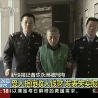 Lights, camera, confession: Chinese journalist Chen Yongzhou is escorted by police officers during a broadcast that showed him confessing to taking money to smear a heavy machinery company in Changsha, China, on Oct. 26 | AP