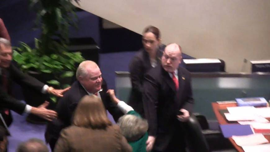 Stampede: Toronto Mayor Rob Ford knocks down Councilor Pam McConnell as he runs toward hecklers in the audience at City Hall on Monday.
