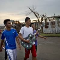 Backing band: A group of friends on Saturday make music in a bid to cheer up residents salvaging their belongings or rebuilding their houses in the Philippine town of Palo. | AFP-JIJI