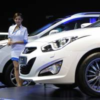 Clean driving: A model stands next to a Hyundai Tucson on display at the Kuala Lumpur International Motor Show in the Malaysian capital on Sunday. In 2014, Hyundai says it will start selling Tucson SUVs powered by a hydrogen fuel cell — the first mass-market vehicle of its type to be sold or leased in the U.S | AP