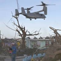 Aid anywhere: A U.S. Marine MV-22 Osprey aircraft flies over damaged buildings as it prepares to land to deliver relief goods for typhoon survivors in Guiuan, Philippines, on Nov. 14. | AP