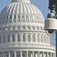 In focU.S.: Surveillance cameras stand on a pole outside the U.S. Capitol in Washington on Oct. 26.   | AP