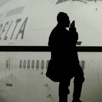 Final call: A traveler waits for a flight in Detroit in October 2012. Fliers have long been barred from using electronic devices while planes are below 10,000 feet because they might interfere with cockpit instruments. | AP