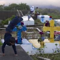 Graveyard play yard: A Nicaraguan boy performs a handstand on the tomb of his relatives at a cemetery in El Crucero on the outskirts of Managua on Saturday | AP