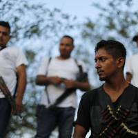 Cartel busters: Men belonging to a vigilante group stand at a checkpoint in the town of Las Colonias, Mexico, on Tuesday. | AP