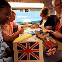 On the move: People take part in an English lesson aboard a high-speed train heading to Paris on Nov. 7. The new service, called 'English on track,' is a pilot program by SNCF state railways to help busy commuters improve their language skills. | AFP-JIJI