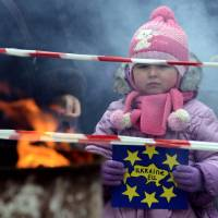For what it's worth: A girl holds a placard reading 'Ukraine-EU' during a pro-European rally in the western Ukrainian city of Ivano-Frankivsk on Monday. | AFP-JIJI