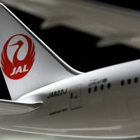 Trimmed: The Japan Airlines Co. logo is seen on the tail fin of a model of a Boeing Co. 787 aircraft displayed in an exhibition area at the company's maintenance center at Haneda International Airport in Tokyo in July. | BLOOMBERG