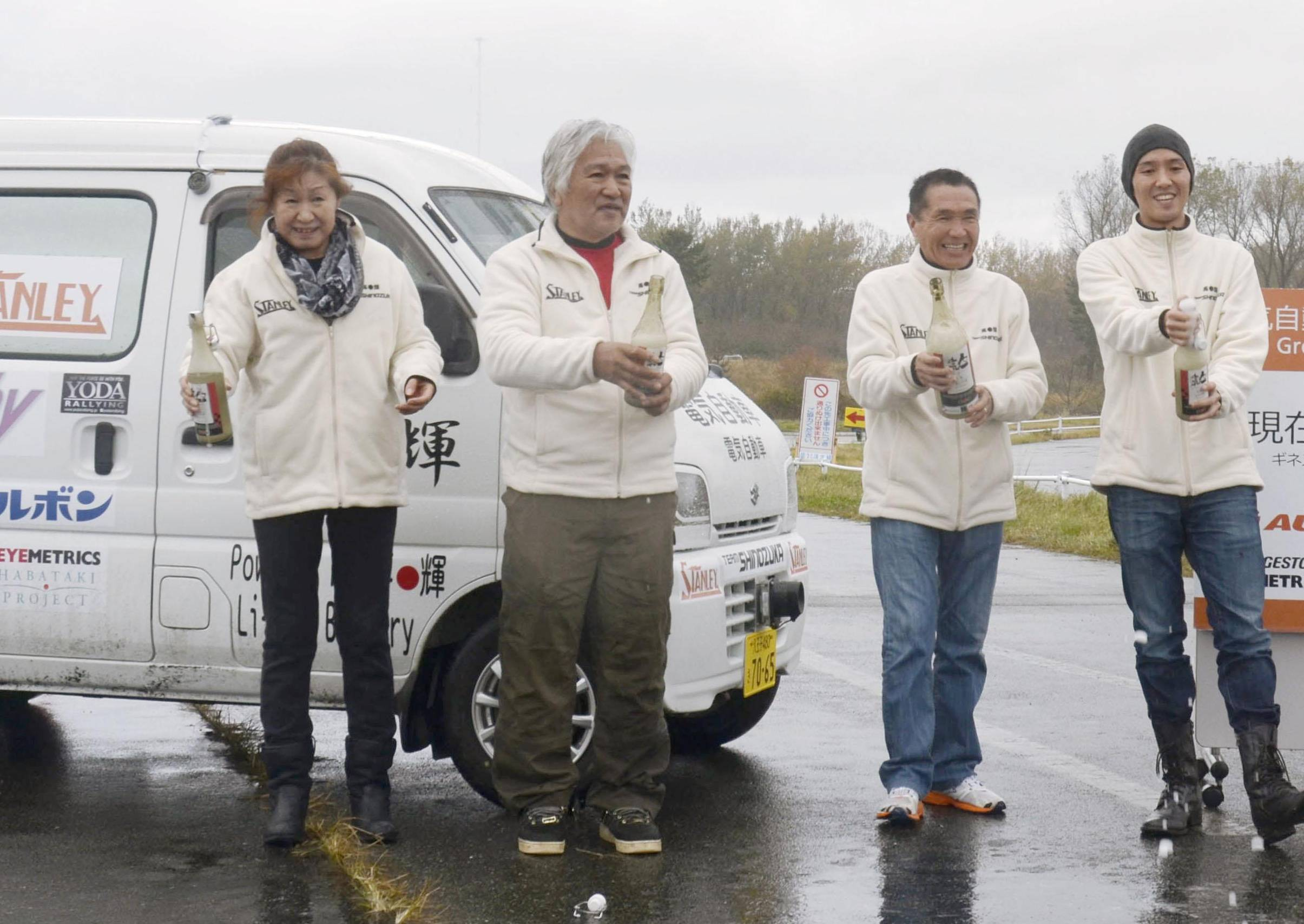 The four-driver team including former Dakar Rally driver Kenjiro Shinozuka (second from left) celebrate as they set a record Friday for distance traveled by an electric vehicle on a single battery charge in Akita Prefecture. | KYODO