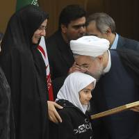 Atomic reaction?: Iranian President Hassan Rouhani kisses the daughter of a nuclear researcher who was assassinated in July 2011 during a news briefing in Tehran on Sunday. | AP