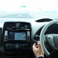 Look, Ma: A Nissan Motor Co. employee takes his hands off the wheel during the carmaker's test of a self-driving vehicle on the Sagami Expressway in Kanagawa Prefecture on Monday. | MASAAKI KAMEDA