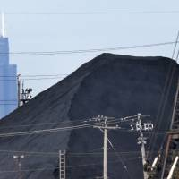 Health hazard: Petroleum coke sits in a residential area of southeast Chicago. In the background is the Willis Tower downtown. | AP