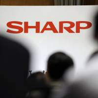 Making changes?: The Sharp Corp. logo appears on a wall during the unveiling of its new TVs in Tokyo in May. | BLOOMBERG