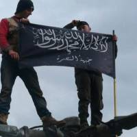 Different mission: Syrian rebels from al-Qaida-linked Jabhat al-Nusra hold the brigade's flag while standing on a Syrian Air Force helicopter at Taftanaz Air Base, in Idlib province, in January | AP