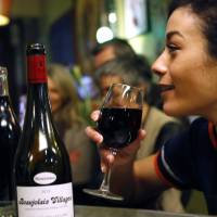 Sensational taste: A woman enjoys a glass of Beaujolais Nouveau in Lille, France, on Thursday. | AP