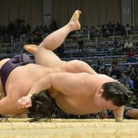 Learning the hard way: Takekaze (left) beats Goeido with a <B><I>shitatenage</I></B> (underarm throw) on Nov. 19 at the Kyushu Grand Sumo Tournament in Fukuoka. | KYODO