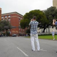 Cross road: Tourists stand in the middle of Dallas' Elm Street last month to take pictures from the spot, marked by a X, where the fatal shot hit President John Kennedy in 1963. They are looking up at the Texas School Book Depository (left). The sixth-floor window where Lee Harvey Oswald fired his rifle is on the right, the second row from the top.  | THE WASHINGTON POST