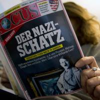 Treasure trove: A journalist on Monday reads an issue of the German weekly magazine Focus featuring an article about the 2011 discovery in a Berlin apartment of valuable artworks allegedly plundered by the Nazis | AFP-JIJI