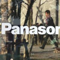 Streamlining: People are reflected in the window of a Panasonic showroom in Tokyo on Wednesday. The company is nearing a deal to sell three domestic semiconductor plants to an Israeli company as it casts off money-losing operations. | AFP-JIJI