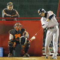 Close attention: Yomiuri's Hayato Sakamoto takes batting practice while manager Tatsunori Hara watches on from behind in Sendai on Friday. | KYODO