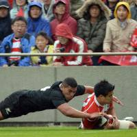 Rout: New Zealand's Charles Piutau tackles Japan's Yu Tamura in Saturday's test match at Chichibunomiya Stadium. The All Blacks won 54-6. | AFP-JIJI
