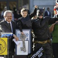 Forget Robin: Dressed as Batkid, Miles Scott, 5, raises his arm next to Batman at a rally outside of San Francisco City Hall with Mayor Ed Lee (left) and his father, Nick, and brother, Clayton, on Friday. Miles was called into service Friday morning by San Francisco Police Chief Greg Suhr to help fight crime, as San Francisco turned into Gotham City to help fulfill the young leukemia patient's wish to transform into the Caped Crusader's tiny sidekick | AP
