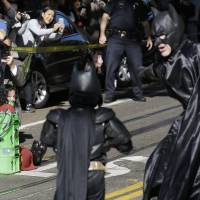 To the rescue: Miles Scott, dressed as Batkid, walks with Batman to rescue a woman in distress Friday in San Francisco. | AP