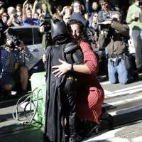 Hero for a day: Dressed as his alter ego, Batkid, 5-year-old Miles Scott rescues a woman in distress in San Francisco on Friday. | AP