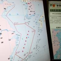 Conflicting claims: Computer screens display a map showing the outline of China's new air defense zone in the East China on the website of the Chinese Ministry of Defense in Beijing on Tuesday. | AP