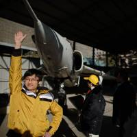 Show of strength: Visitors pose before a decommissioned Chinese A-5 ground attack aircraft at the Military Museum in Beijing on Thursday. | AFP-JIJI