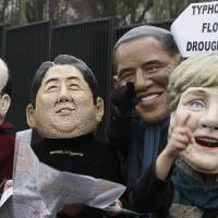 Looking for a deal: Climate activists spoof world leaders (from left) French President Francois Hollande, Prime Minister Shinzo Abe, U.S. President Barack Obama and German Chancellor Angela Merkel in front of the U.N. climate change conference at the National Stadium in Warsaw on Friday. | AP