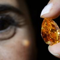 Orange to green: A model holds up 'The Orange,' a 14.82-carat pear-shaped diamond during a news preview on Oct. 31 in Geneva. The orange diamond, the largest known of its kind, went under the block Tuesday in the Swiss city, fetching $31.5 million | AFP-JIJI