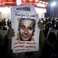 Programmed to protest: A supporter of Egyptian Defense Minister Gen. Abdel-Fattah el-Sissi holds a poster showing Bassem Youssef and reading, 'Not Egypt, you are degrading to the media, fifth column' during a protest in Cairo on Wednesday | AP