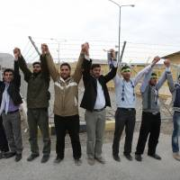 Atomic ire: Iranian students chant slogans as they join hands while forming a human chain around the Isfahan Uranium Conversion Facility in support of Iran's nuclear program, as one of them holds a poster of late revolutionary founder Ayatollah Ruholla Khomeini, just outside the city of Isfahan, Iran, in November 2011. | AP
