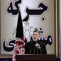 Defiant: Afghan President Hamid Karzai delivers a speech on the first day of the Loya Jirga in Kabul on Thursday. An aid to Karzai said he plans to defy U.S. threats to sign a bilateral security deal before spring elections. | AP