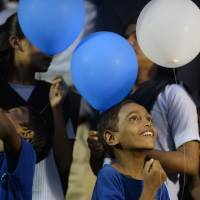 Healing ritual: Indian children hold balloons during a gathering in Mumbai on Friday to pledge for peace in memory of the people who lost their lives in the 2008 terrorist attacks on the city. A total of 166 people were killed and more than 300 others were injured when 10 heavily-armed Islamist militants stormed the city on Nov. 26, 2008, attacking sites that included the main railway station, two luxury hotels, a popular tourist restaurant and a Jewish center. | AFP-JIJI