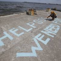 In desperate need: A survivor writes a message appealing for help at a port in the typhoon-ravaged Philippine city of Tacloban on Monday   AP