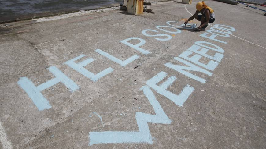 In desperate need: A survivor writes a message appealing for help at a port in the typhoon-ravaged Philippine city of Tacloban on Monday
