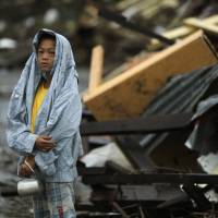 Survivor: A boy, surrounded by debris left in the wake of Typhoon Haiyan, waits on the side of the road for fresh water in  Tacloban on Tuesday | AP