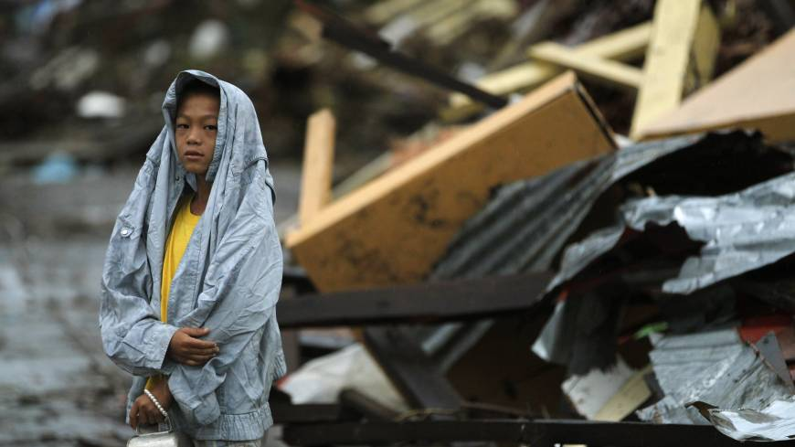 Survivor: A boy, surrounded by debris left in the wake of Typhoon Haiyan, waits on the side of the road for fresh water in  Tacloban on Tuesday